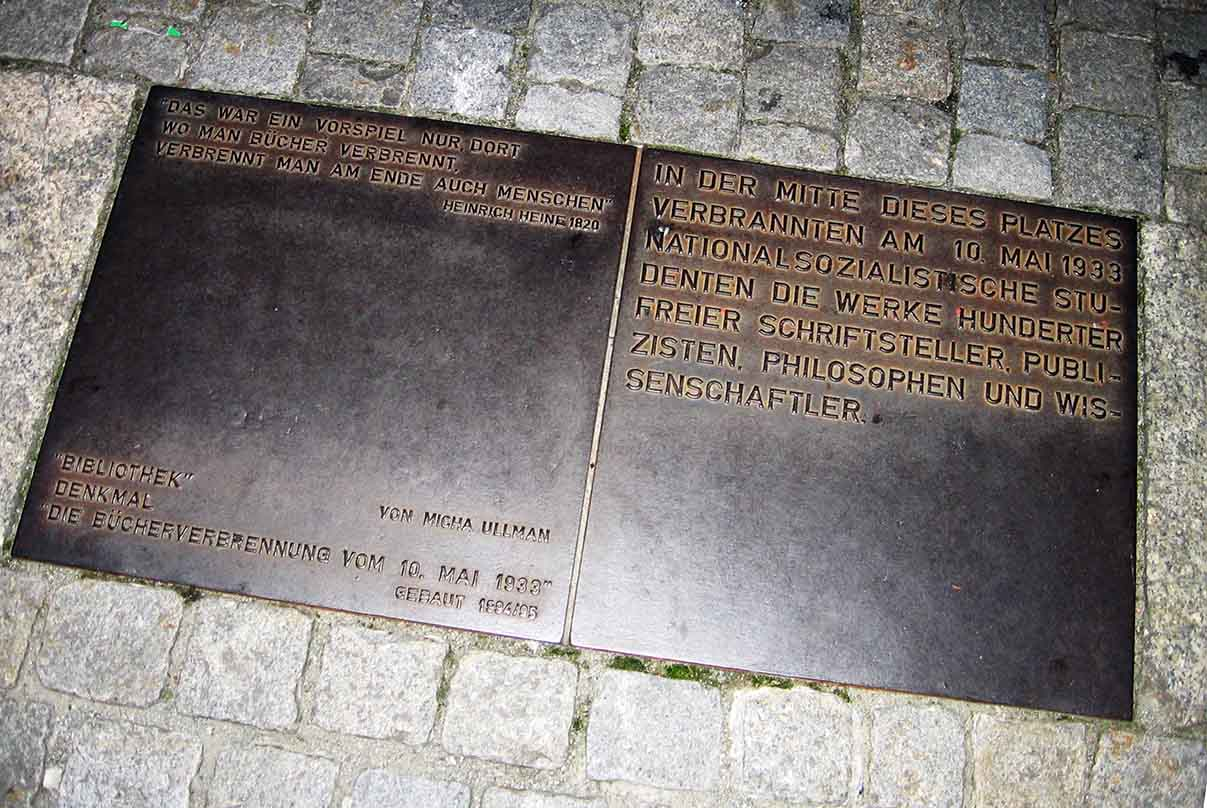 """The plaque accompanying the memorial comprises Heine's quote, the artist's name and the event: """"On May 10, 1933, in the middle of this square, National Socialist students burnt the works of hundreds of authors, journalists. philosophers and academics. - <em>by SL Wong</em>"""