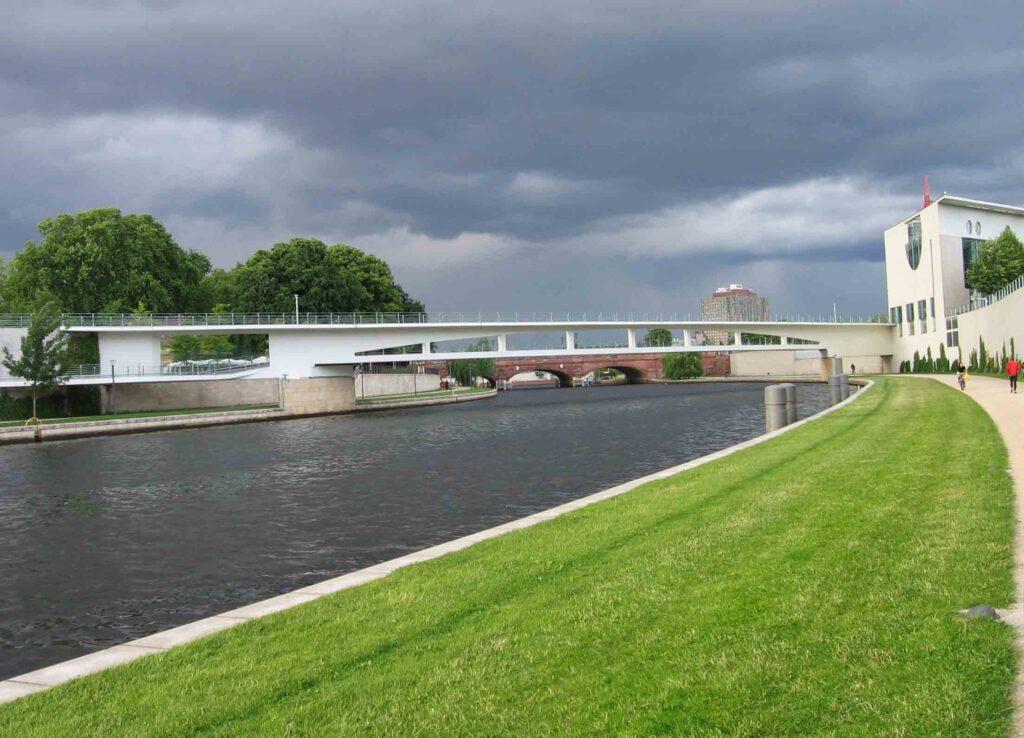 A rainy-gray Spree winding under the Nordbrücke am Bundeskanzleramt and the red-brick Moltke Bruecke behind. - <em>by SK Mandal</em>