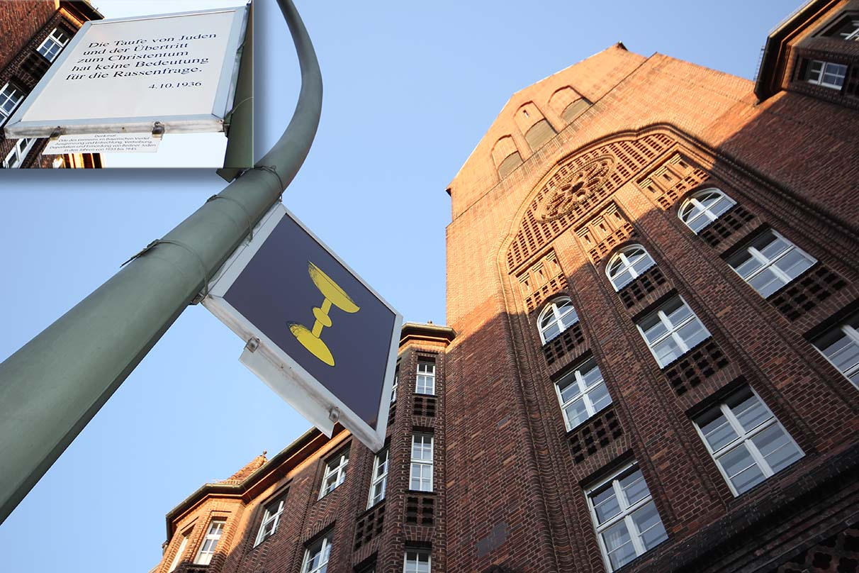 This sign near a church states that conversion to Christianity would have no bearing on race. The regulation was formulated in 1939, the year Jews were obligated to wear the yellow badge. - <em>by SL Wong</em>